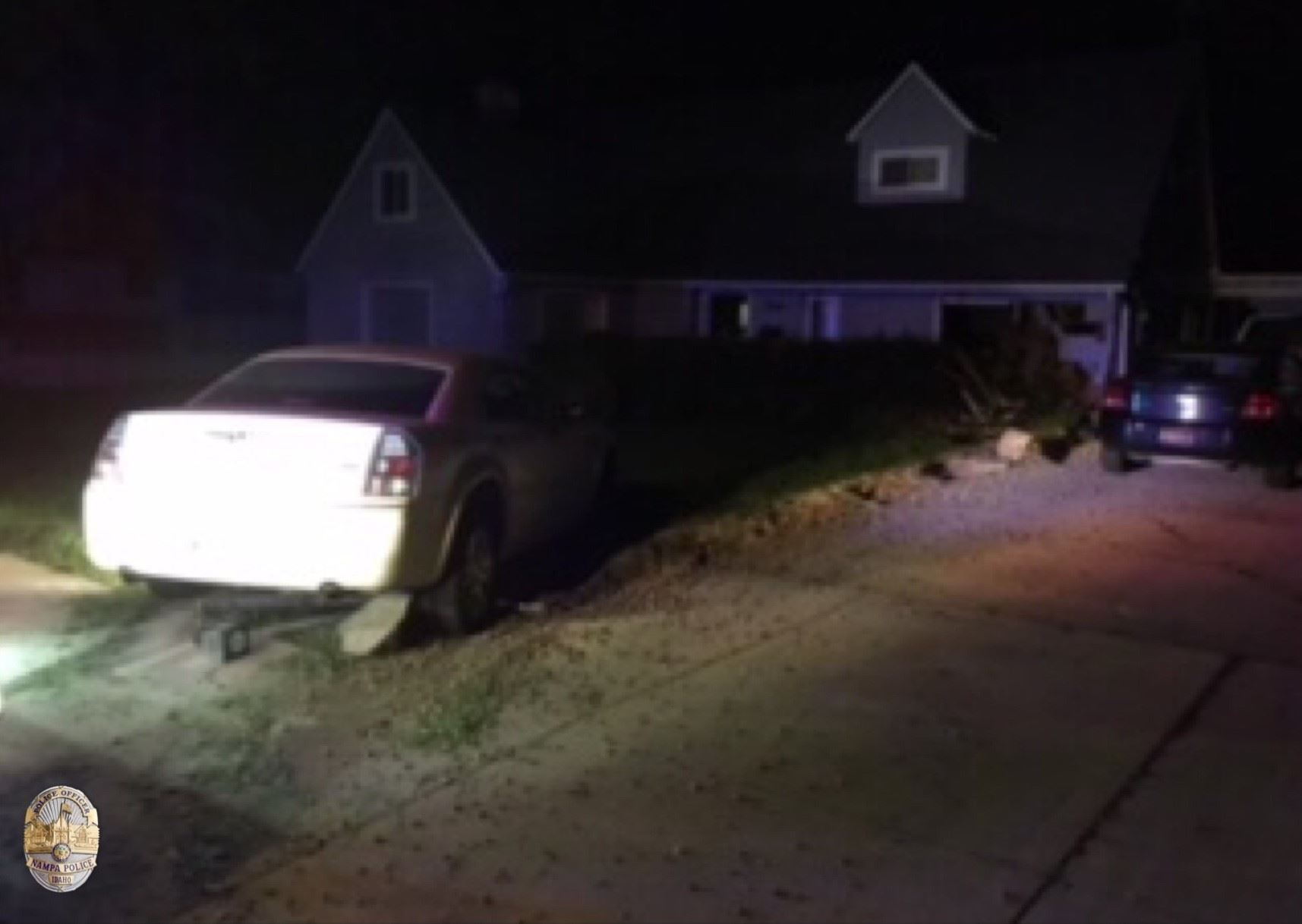 Photo of vehicle involved in crash stuck in the front yard of the residence.